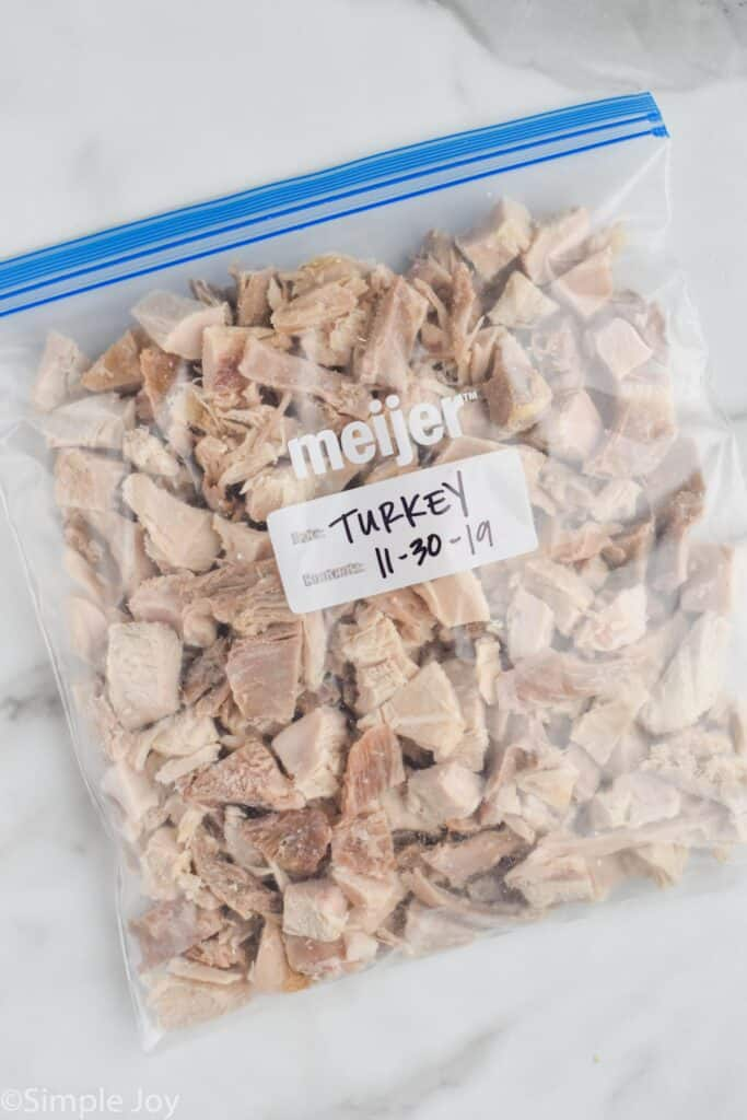 a plastic storage bag full of frozen turkey cut into bite sized pieces