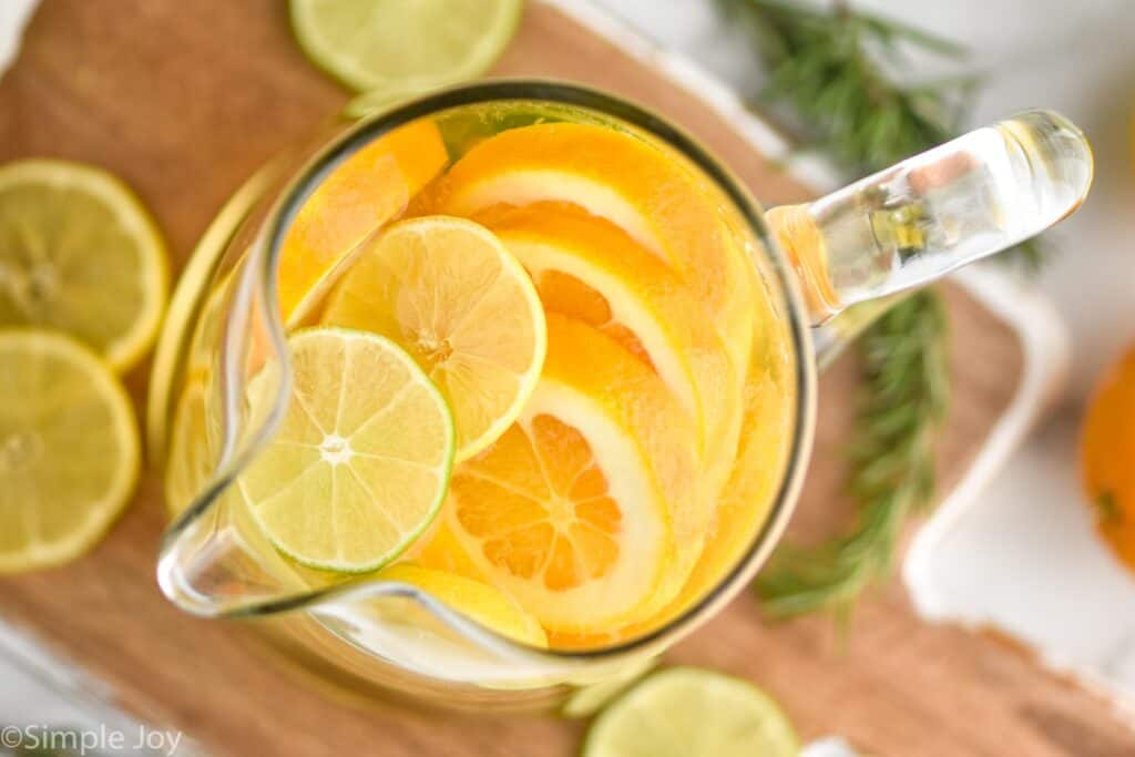 overhead view of a pitcher of white wine sangria with cut up limes, lemons and oranges visible