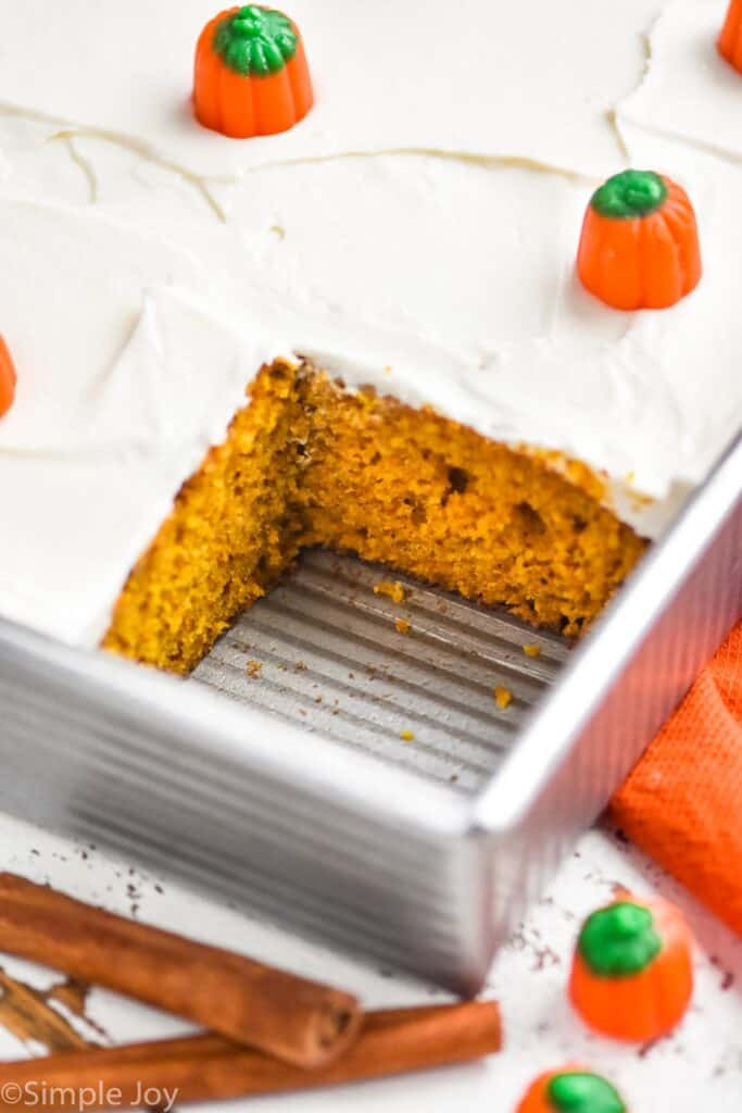 close up of a pumpkin cake in a metal baking dish that has been cut into