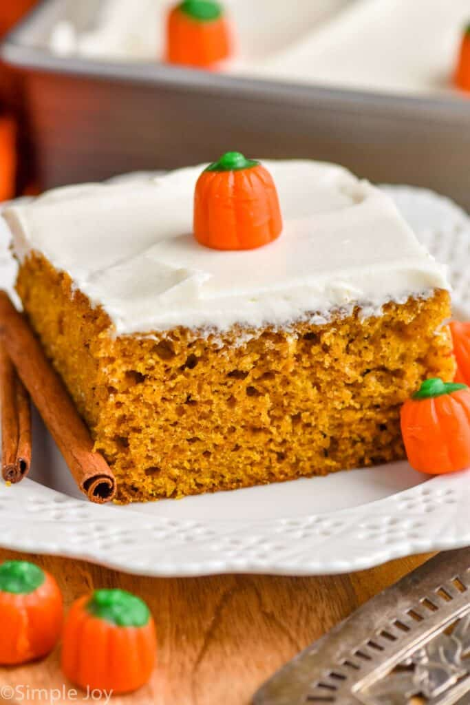 close up picture of a piece of pumpkin cake topped with cream cheese frosting on a plate