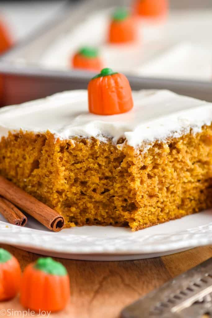 close up picture of a pumpkin cake with cream cheese frosting with a bite missing