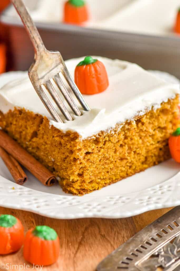 a fork pushing into a piece of pumpkin pie cake topped with cream cheese frosting