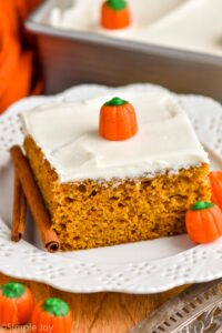 a piece of pumpkin pie cake topped with cream cheese frosting on a plate with candy pumpkins and cinnamon sticks
