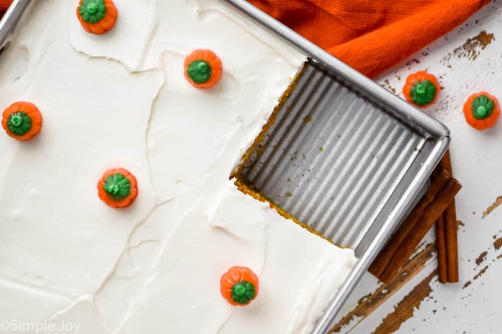 overhead view of a pumpkin spice cake in a baking dish topped with cream cheese frosting and small pumpkin candies