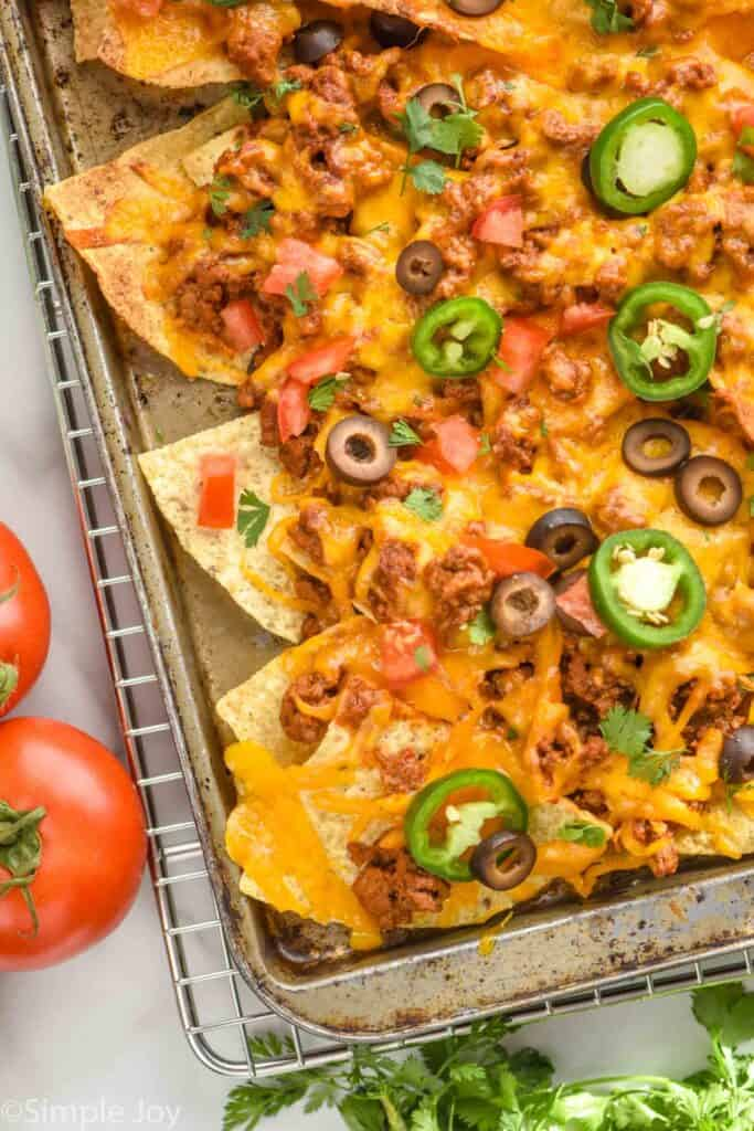 close up overhead view of sheet pan nachos topped with olives, diced tomatoes, and jalapeño slices