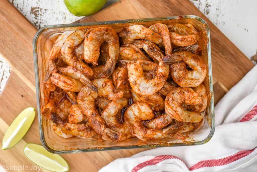 overhead view of shrimp marinating in shrimp fajita seasoning in a glass container