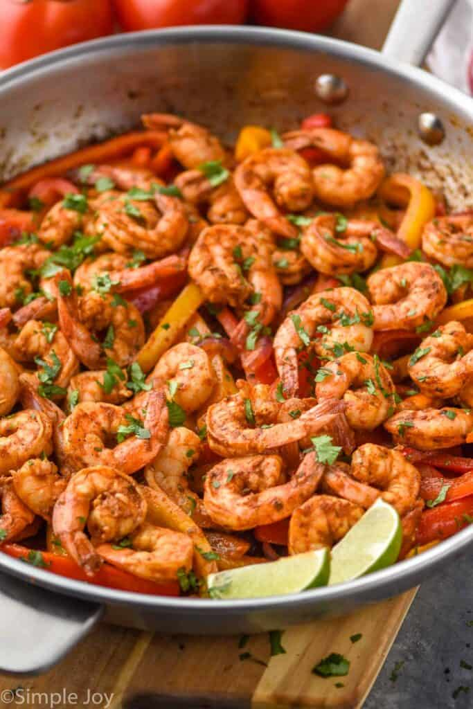 a frying pan full of shrimp fajita recipe topped with fresh cilantro and two lime wedges