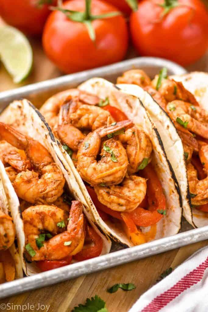 three shrimp fajitas on a metal tray garnished with fresh cilantro