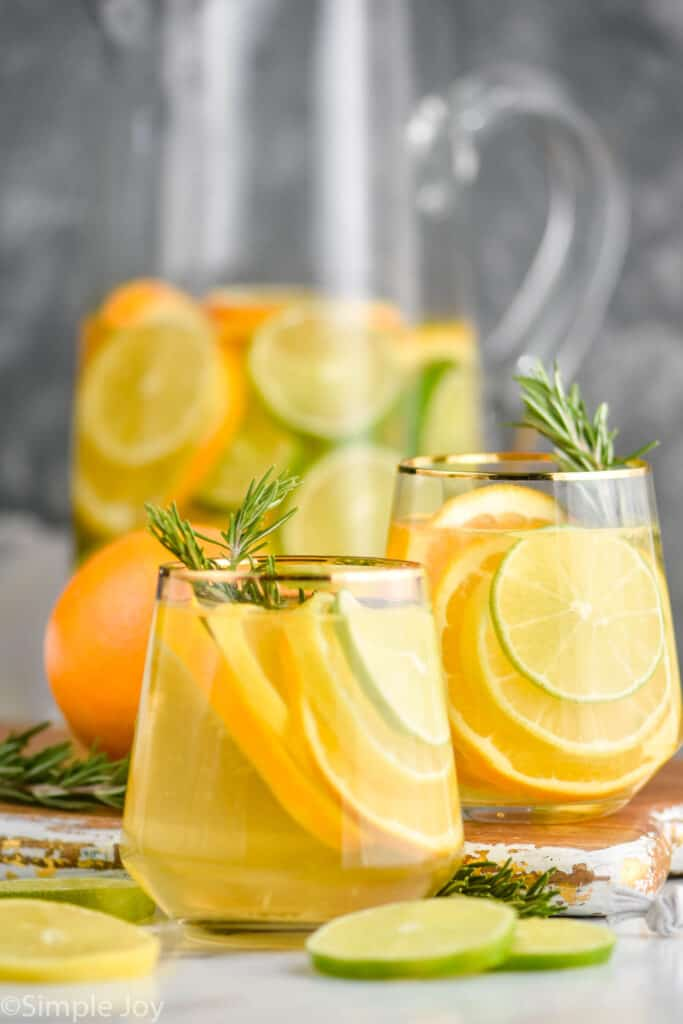 two glasses of white sangria recipe with the pitcher in the background