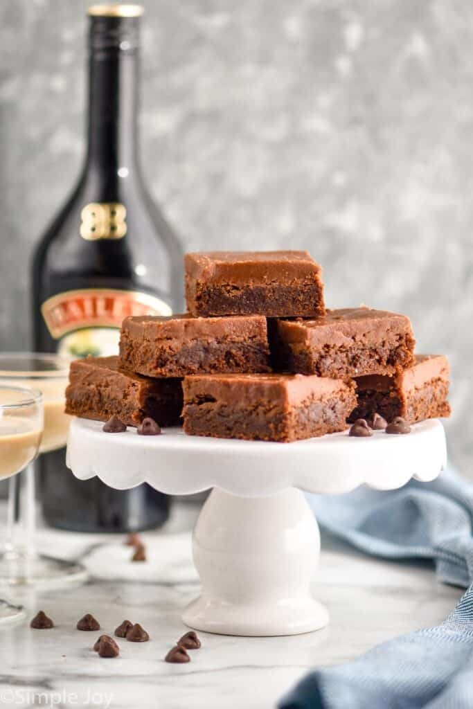 a pile of brownies on a white cake platter with baileys Irish cream in the background