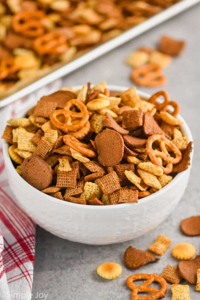big white bowl of Chex mix with the baking sheet in the background