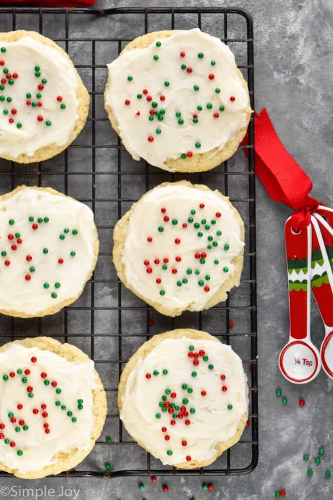 overhead view of 6 sour cream cookies that are frosted and on a cooling rack with red and green sprinkles