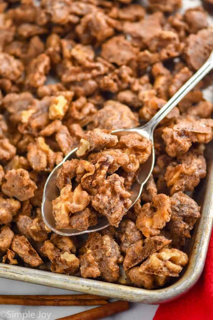 a spoon dishing up candied walnuts recipe from a baking sheet