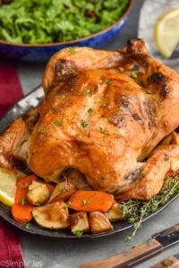 close up of a roast chicken on a platter surrounded by vegetables