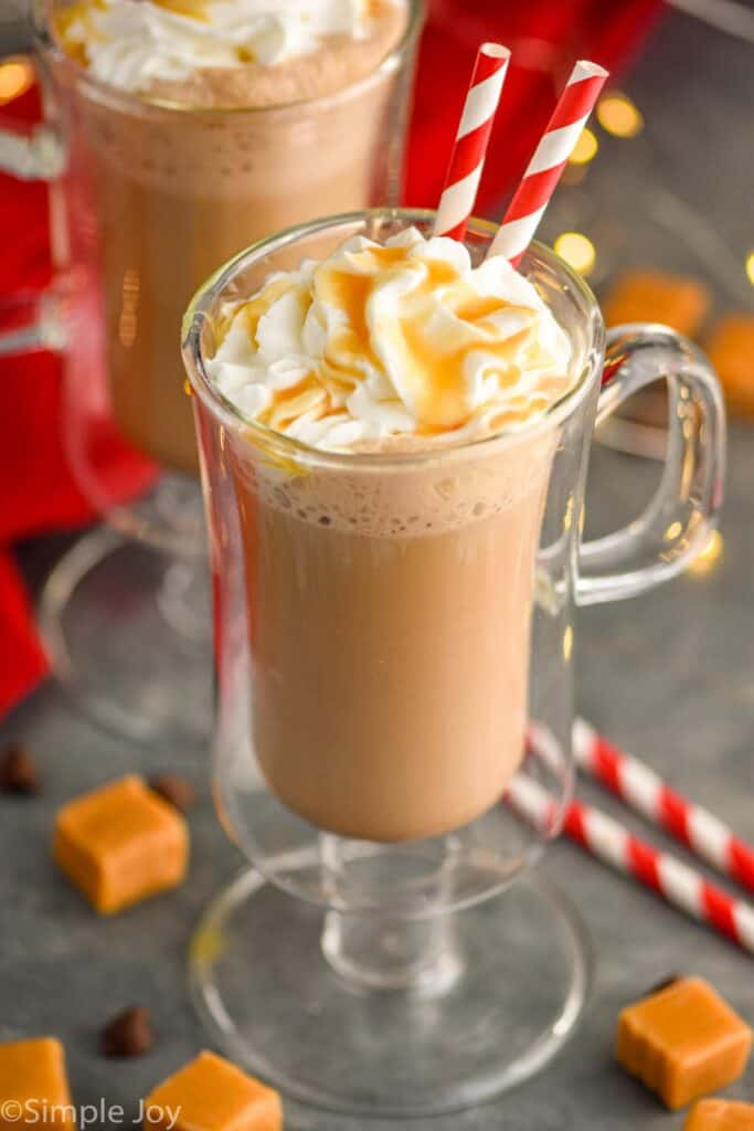 two glasses of salted caramel mocha with whipped cream and caramel topping, two straws sticking out