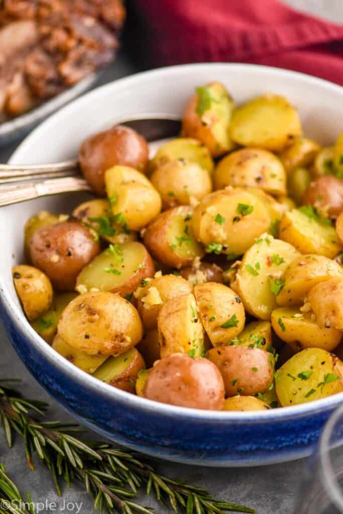 small potatoes recipe garnished with parsley in a serving bowl