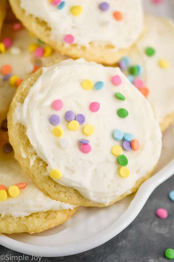 close up of a sour cream cookie on a plate that has been frosted and decorated with sprinkles