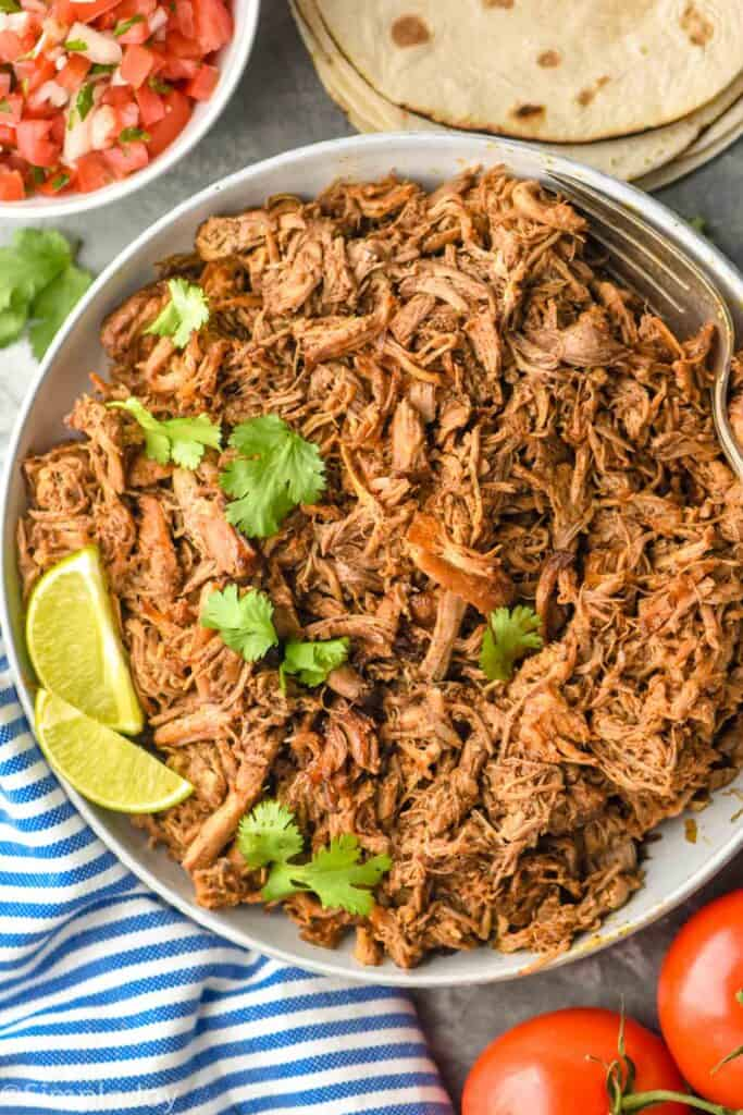 overhead view of slow cooker carnitas meat that has been garnished with two limes and fresh cilantro