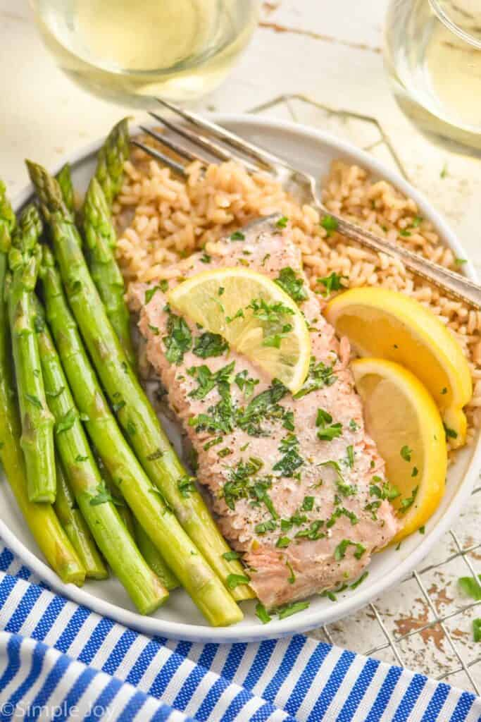 a baked salmon filet on a plate with asparagus and brown rice