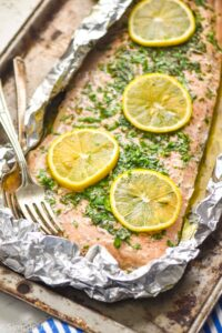 side view of baked salmon in foil that has been topped with lemon slices and fresh parsley