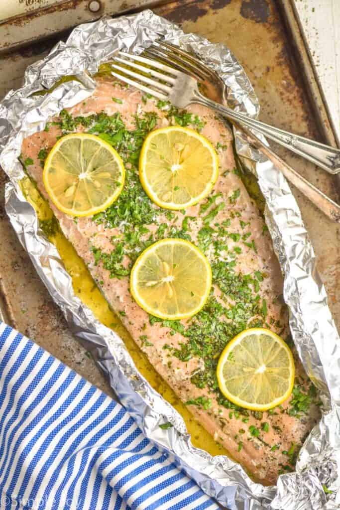 overhead view of baked salmon recipe that is in foil and topped with lemon slices fresh parsley and has two forks next to it