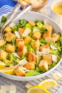 side view of a Caesar salad in a bowl with large croutons and peels of Parmesan cheese