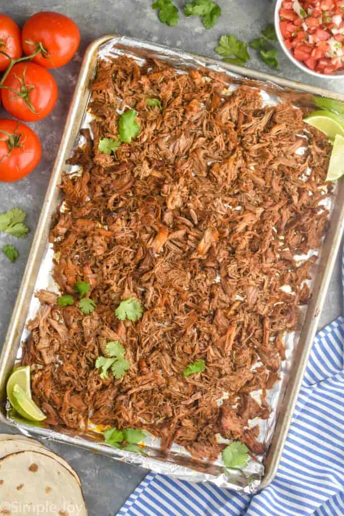 baking sheet full of the pulled meat from a carnitas recipe topped with fresh cilantro and two limes