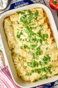overhead photo of green enchiladas in a casserole dish topped with cilantro