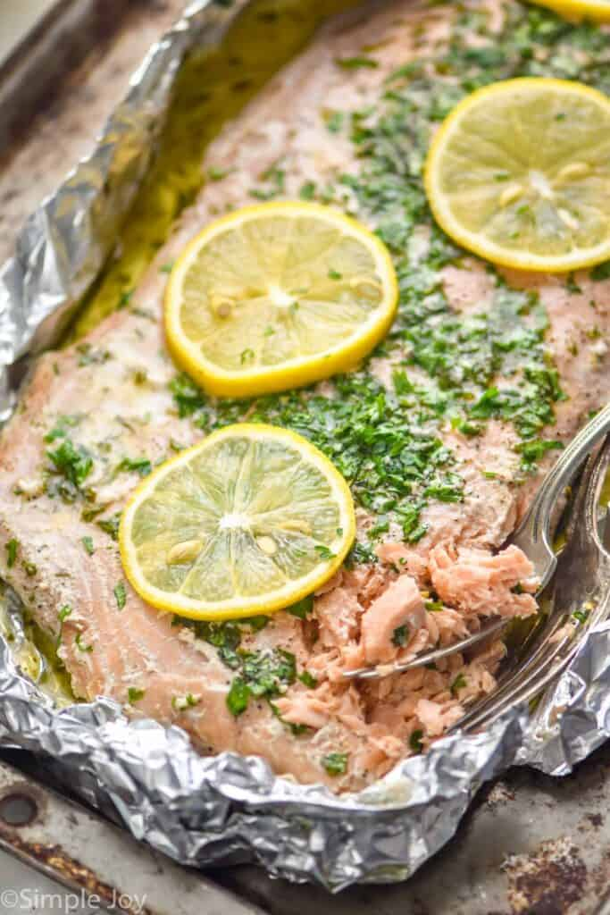 oven baked salmon in foil topped with lemon slices and parsley that has been lightly flaked by two forks