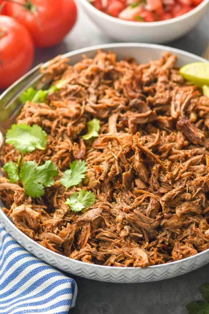 bowl of slow cooker pork carnitas meat that has been garnished with cilantro and limes