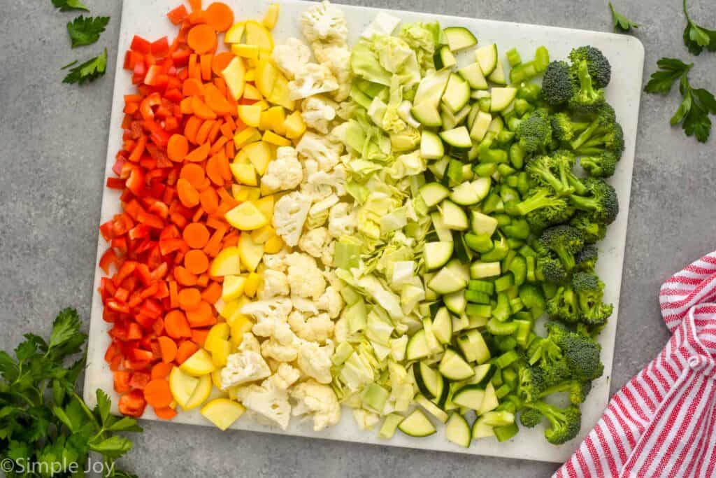 overhead view of vegetables chopped up to make vegetable soup on a cutting board in rainbow order