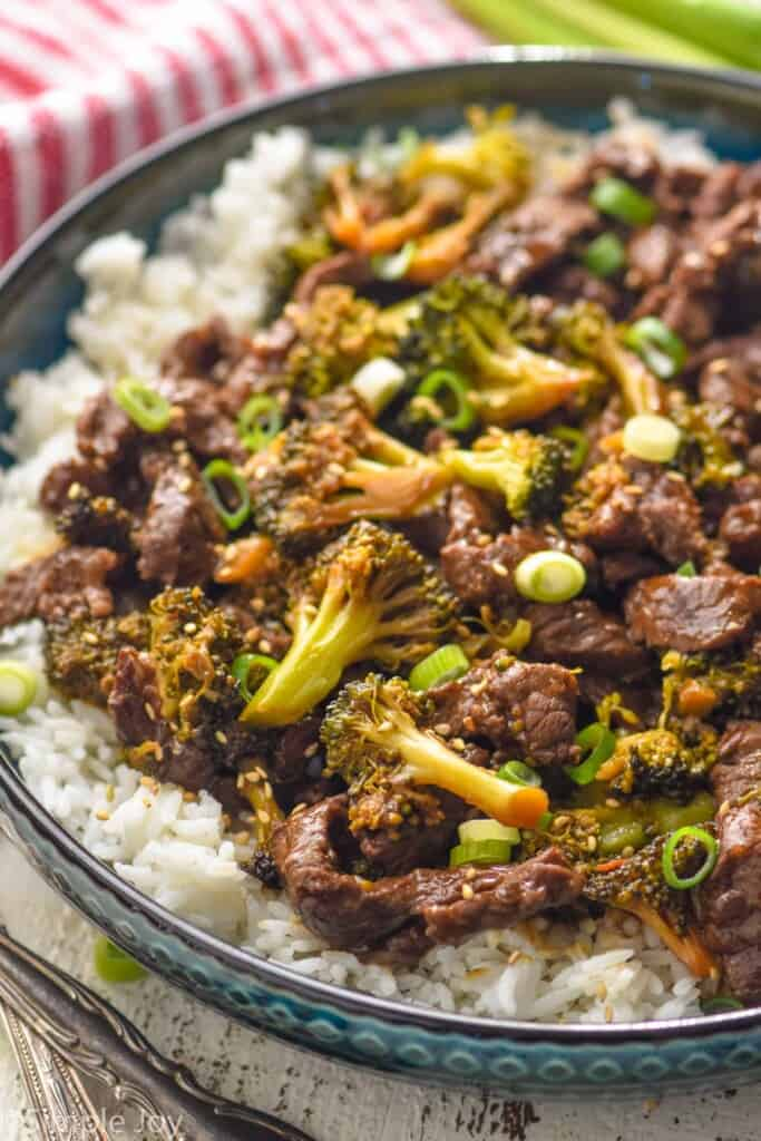side view of a bowl of beef and broccoli over rice garnished with sesame seeds and sliced scallions