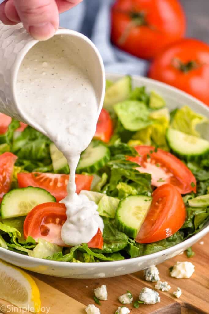 best blue cheese dressing being poured onto a salad
