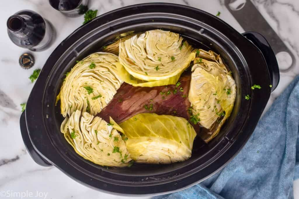 overhead photo of cabbage covering corned beef in a crockpot