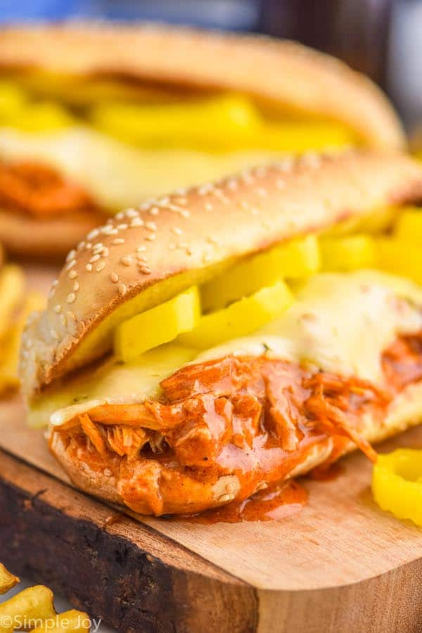 close up of a crockpot buffalo chicken sandwich on a hoagie roll with melted cheese and pepper rings