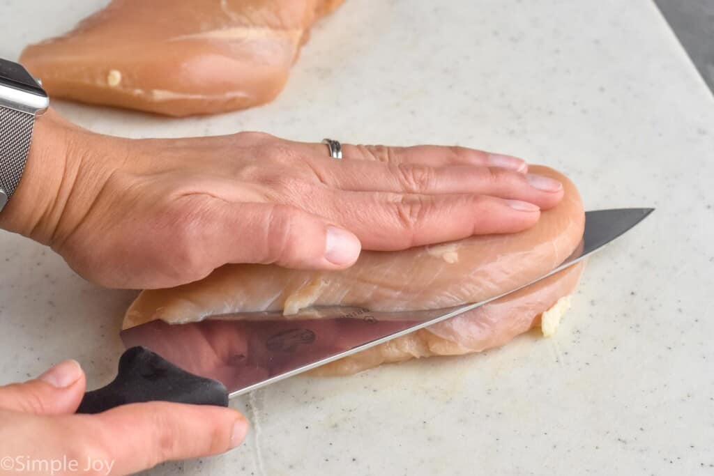 a hand on top of a chicken breast as a knife cuts it in half to make chicken cutlets