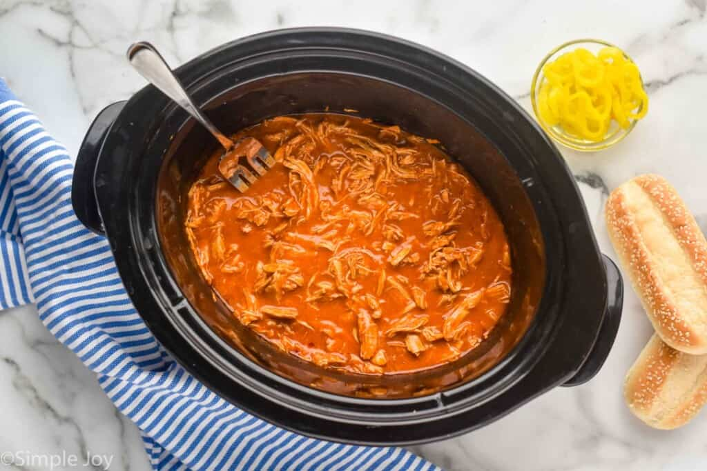 overhead view of a slow cooker full of shredded buffalo chicken