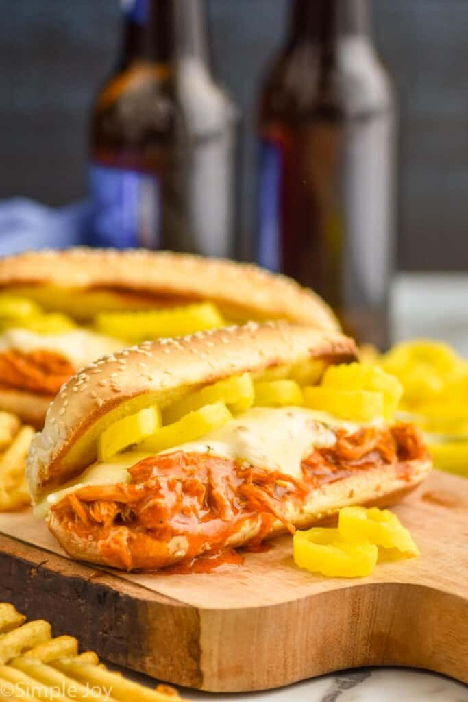 crockpot buffalo chicken sandwich with cheese and pepper rings on a cutting board