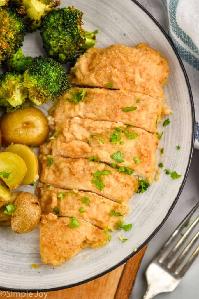 plate with a piece of sour cream chicken cut into slices next to broccoli and roasted potatoes