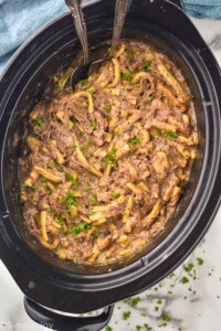 overhead photo of a slow cooker full of beef and noodles
