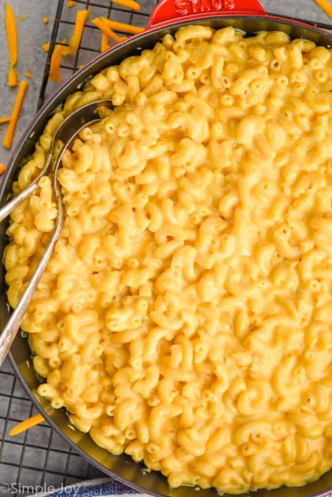 close up overhead view of Mac and cheese recipe in a skillet with two spoons dug in