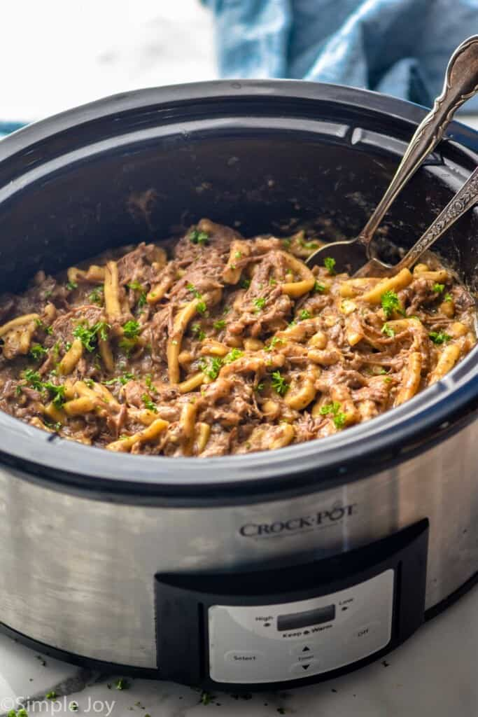 side view of a crockpot full of beef and noodles