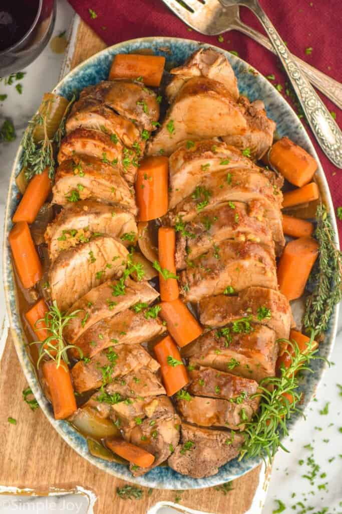 overhead of slow cooker pork tenderloin sliced an on a platter with cooked carrots