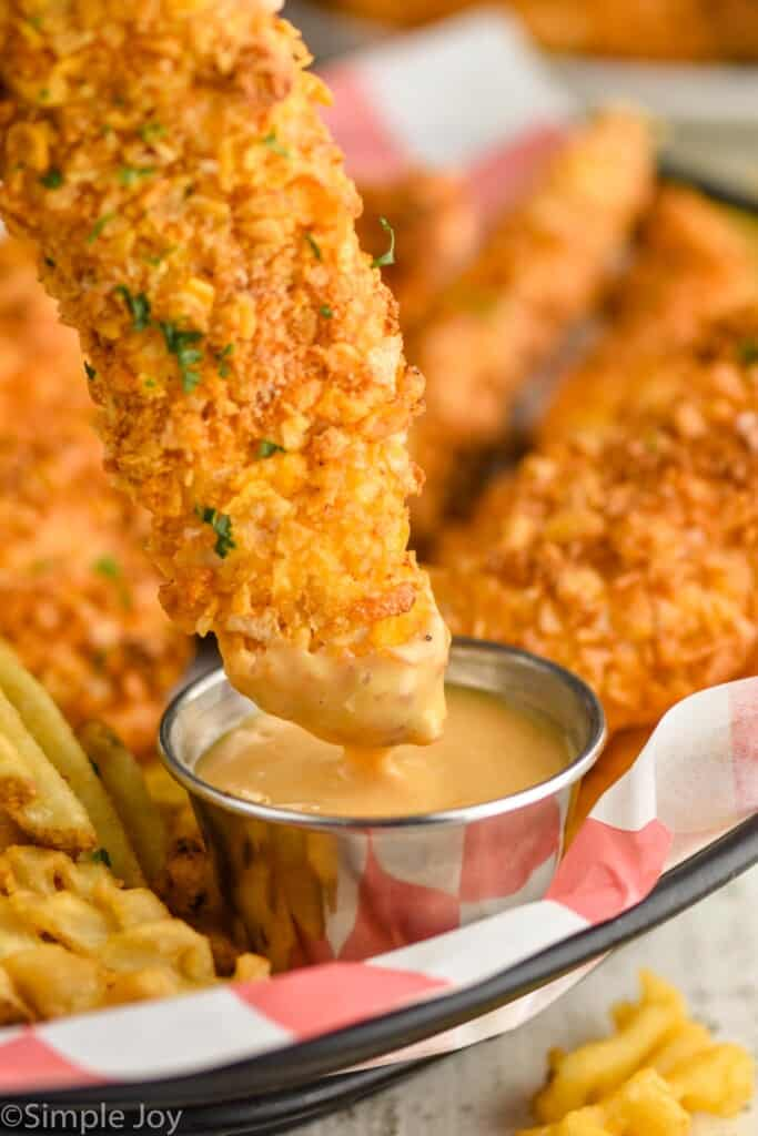 chicken strip being dipped into chick fil a sauce