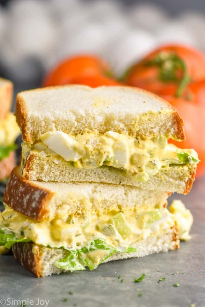 an egg salad sandwich that has been cut in half and stacked