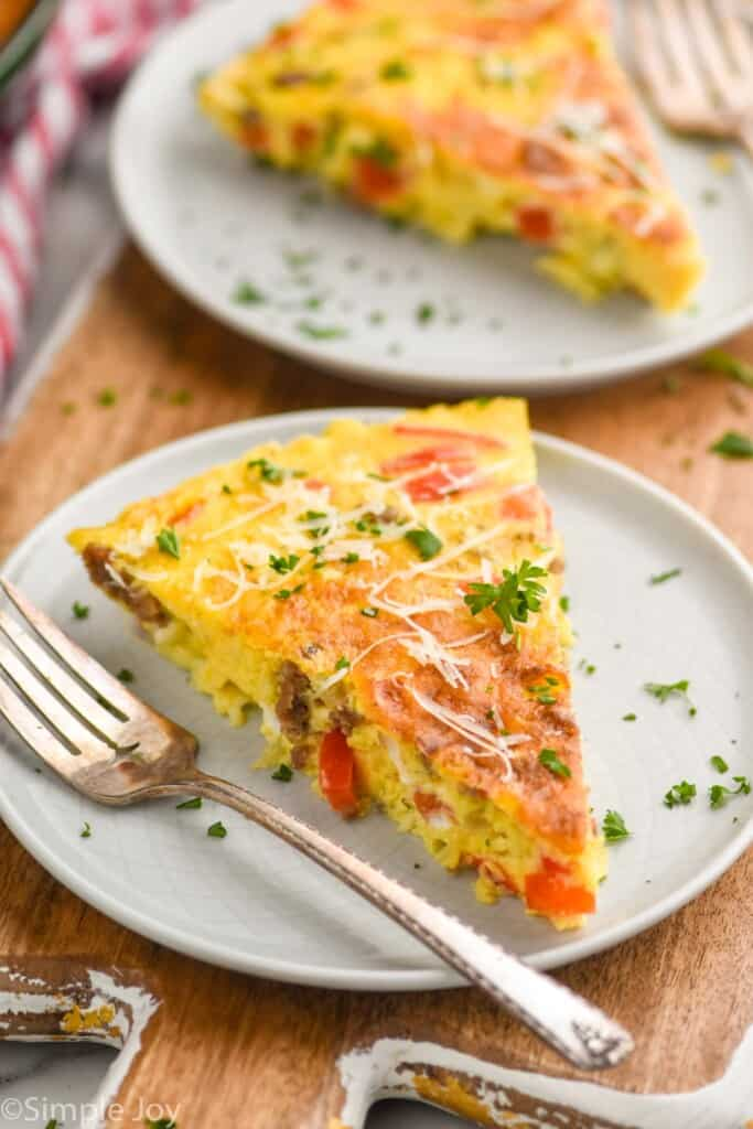 close up picture of a frittata recipe on a white plate garnished with parsley and parmesan