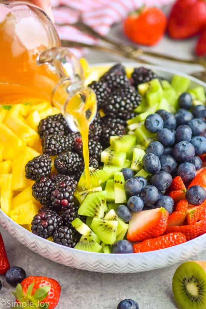 fruit salad dressing being poured over fruit in a bowl