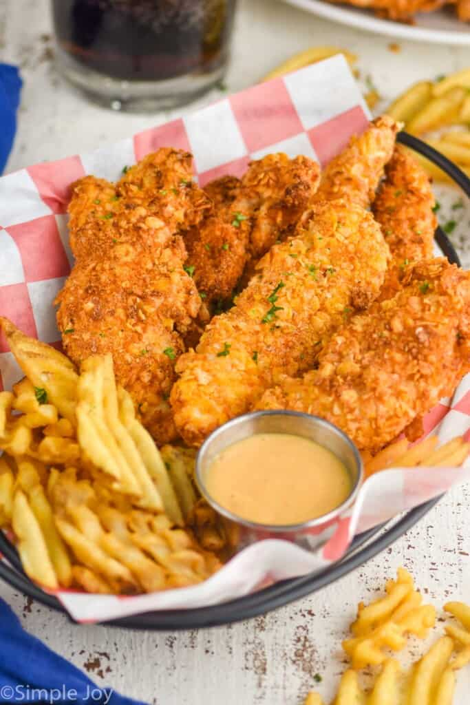 chicken tenders in a basket with fries and chick fil a sauce