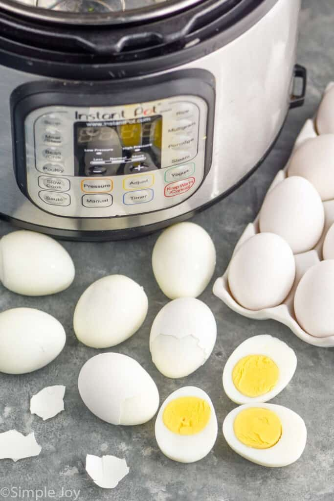 hard boiled eggs in front of an instant pot, some peeled, some cut in half