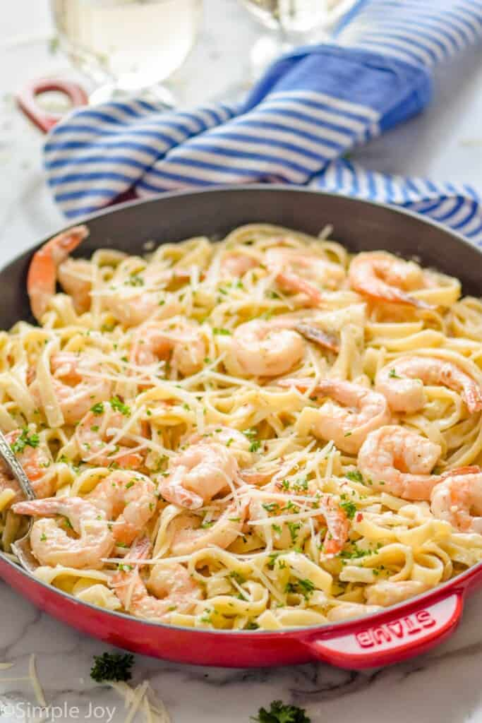 side view of a red skillet full of shrimp pasta recipe garnished with parmesan and parsley